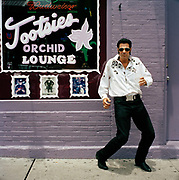 "Johnny Ville ( possible Elvis wannabe)  showing  his moves  outside  the  world famous Tootsies  bar on  Broadway has come to Nashville to develop his musical career: a natural performer and self promoter ""Elvis was my daddy""  and ""I've only been down to Nashville for a week and I've already got myself a record deal"" he claims,  Johnny doesn't have a permanent address and seems to rove around trying to make a few bucks with his guitar. It seems the romantic spirit of Nashville is alive and well. Nashville is the capital of Tennessee  and the self styled  home of country  music. Today There is still some great music to be found but one has to navigate some typical  US commercialism  in the search as  the town cashes in on its reputation."