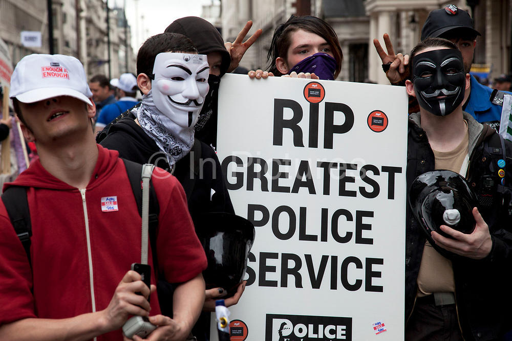 Occupy LSX members in support of the police with placards and wearing plastic police helmets. On a day when 400,000 public sector workers go on strike over cuts, pay and pensions, approximately 30,000 off duty police officers, marched in the capital against projected job losses over the next four years. London, UK.