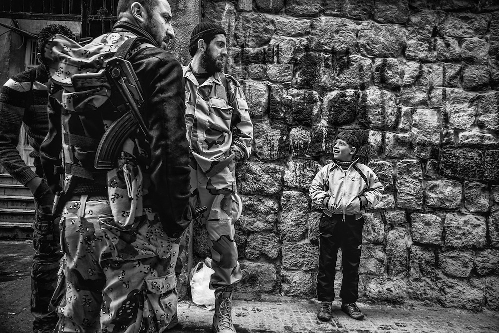 A boy looks up at commanders of the Free Syrian Army as they talk about upcoming military operation.