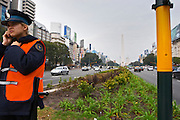The obelisk, obelisco, on the Plaza de la Republica Square on the Avenida 9 Julio Avenue of ninth of July, a woman police man in the foreground. Traffic. Modern office buildings. Buenos Aires Argentina, South America