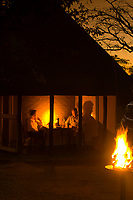 A couple eating dinner outside their bungalow by candlelight, Prestoriuskop Camp, Kruger National Park, South Africa