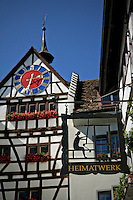 Blue skies shine brightly above this Tudor style looming building and clock located in Stein am Rhein, Switzerland