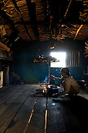 An old Bahnar ethnic woman takes care of the fireplace in a traditional wooden house. Pleiku, Vietnam, Asia