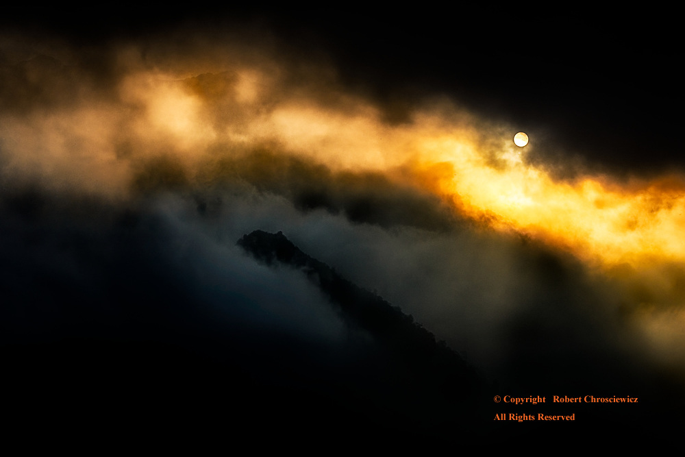 Ring of Light: Light of an early sunset radiates through a heavy fog and round a volcanic peak, Sapa Vietnam.