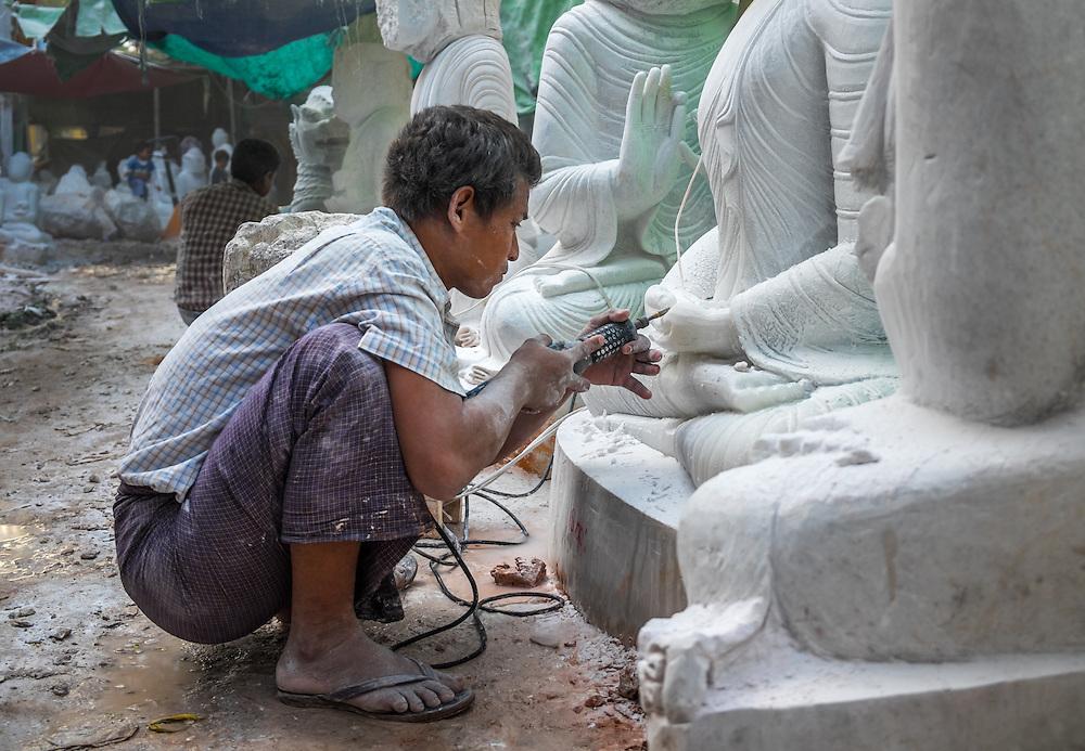 MANDALAY, MYANMAR - CIRCA DECEMBER 2013: Young man carving an image of Buddha marble in a workshop in Mandalay, Myanmar