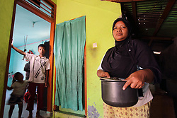 Julita 33 years and  daughet Nurul Naira 4 and son Aris 12 years in the kitchen of their home.  In Lhok Seudu Village where Oxfam had built shelter following the Indian Ocean Tsunami of Dec 2004, District Aceh Besar, Aceh Province, Sumatra, Indonesia