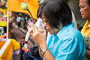 12 APRIL 2013 - BANGKOK, THAILAND:   . A Thai woman prays before sprinkling scented oils on the Phra Buddha Sihing on the first day of Songkran in Bangkok. The Phra Buddha Sihing, a revered statue of the Buddha, is carried by truck through the streets of Bangkok so people can make offerings and bathe it in scented oils. Songkran is celebrated in Thailand as the traditional New Year's Day from 13 to 16 April. The date of the festival was originally set by astrological calculation, but it is now fixed. If the days fall on a weekend, the missed days are taken on the weekdays immediately following. Songkran is in the hottest time of the year in Thailand, at the end of the dry season and provides an excuse for people to cool off in friendly water fights that take place throughout the country. The traditional Thai New Year has been a national holiday since 1940, when Thailand moved the first day of the year to January 1. The first day of the holiday period is generally the most devout and many people go to temples to make merit and offer prayers for the new year. PHOTO BY JACK KURTZ