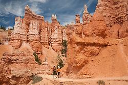 North America, United States, Utah, Bryce Canyon National Park, people hiking below hoodoo rock formations