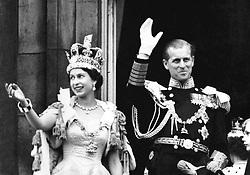 Queen Elizabeth II wearing the Imperial State Crown and the Duke of Edinburgh in uniform of Admiral of the Fleet wave from the balcony to the onlooking crowds around the gates of Buckingham Palace after the Coronation.