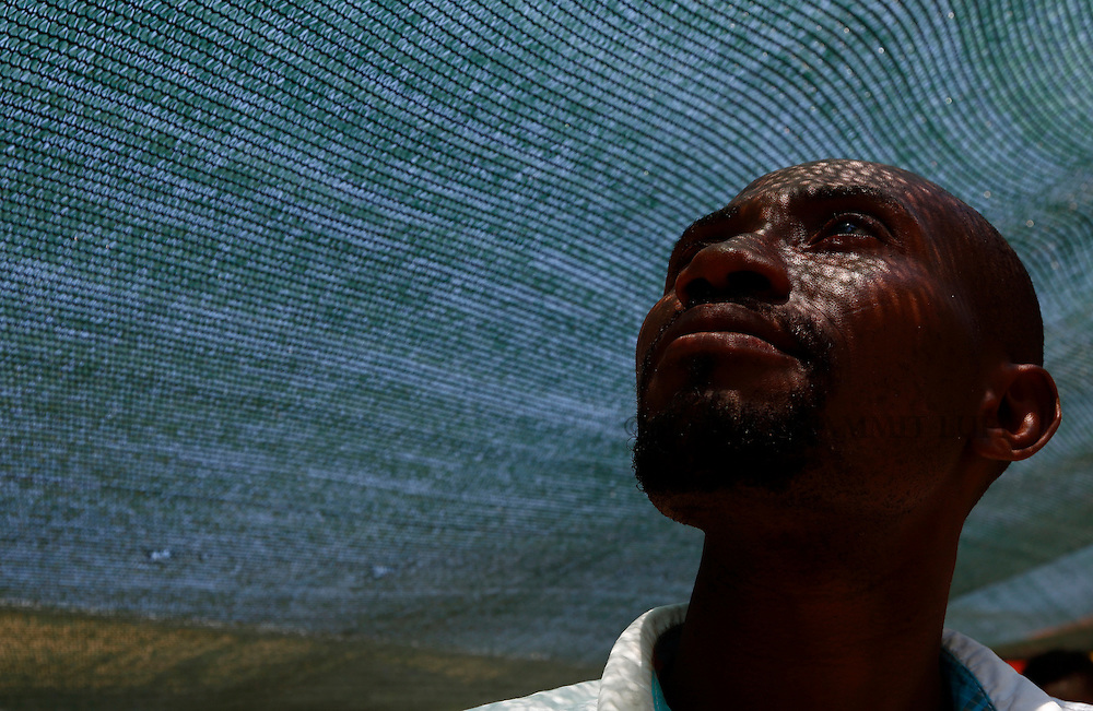A Nigerian migrant shelters from the sun on the deck of the Medecins san Frontiere (MSF) rescue ship Bourbon Argos somewhere between Libya and Sicily August 8, 2015.  Some 241 mostly West African migrants on the ship are expected to arrive on the Italian island of Sicily on Sunday morning, according to MSF.<br /> REUTERS/Darrin Zammit Lupi <br /> MALTA OUT. NO COMMERCIAL OR EDITORIAL SALES IN MALTA