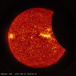Image of the Moon transiting across the Sun, taken by SDO in 304 angstrom extreme ultraviolet light on August 21, 2017.<br /> <br /> Credit: NASA/SDO  Please note: Fees charged by the agency are for the agency's services only, and do not, nor are they intended to, convey to the user any ownership of Copyright or License in the material. The agency does not claim any ownership including but not limited to Copyright or License in the attached material. By publishing this material you expressly agree to indemnify and to hold the agency and its directors, shareholders and employees harmless from any loss, claims, damages, demands, expenses (including legal fees), or any causes of action or allegation against the agency arising out of or connected in any way with publication of the material.