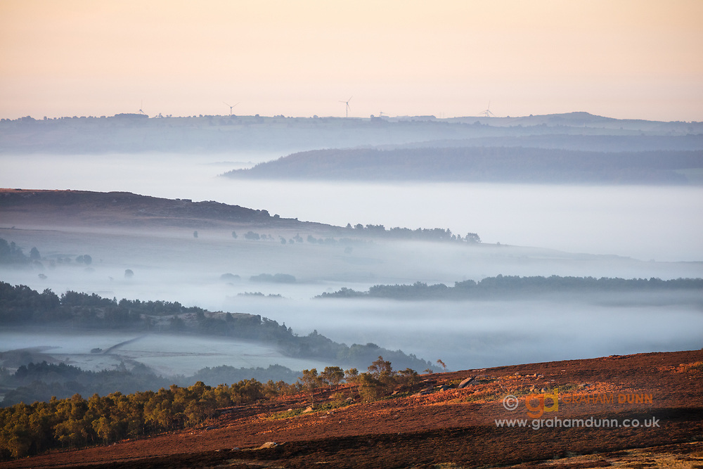 First light adds warmth to the foreground moorland, (situated below Over Owler Tor), whilst a mist-filled Derwent Valley creates a beautifully layered landscape in the distance. A temperature inversion at sunrise in the Derbyshire Peak District, England, UK.