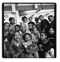 2/19/03 Boris Henderson (cntr), a Wachovia employee, reads to Patricia Dowdy's Double Oaks Pre-Kindergarten class. Henderson, who once lived near the Double Oaks neighborhood, is part of the bank's volunteer program.  L.MUELLER/staff photo