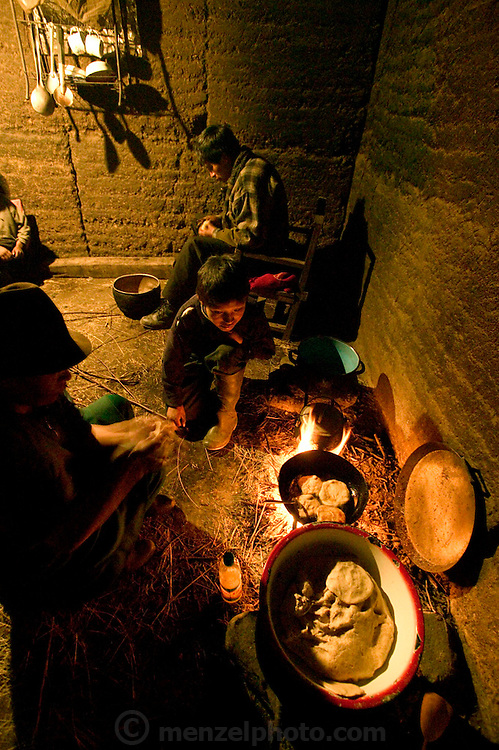 (MODEL RELEASED IMAGE). Ermelinda Ayme cooks empanadas for her children in the family's earthen kitchen house in Tingo, Ecuador, as one of her sons' watches. Husband Orlando slices onions to help his wife, an unusual task for a village man to undertake in Ecuador. (Supporting image from Hungry Planet: What the World Eats)
