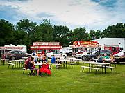 "26 JUNE 2020 - DES MOINES, IOWA: People social distance while they picnic at Fair Food Friday in Des Moines. The 2020 Iowa State Fair, like many state fairs in the Midwest, has been cancelled this year because of the COVID-19 (Coronavirus) pandemic. The cancellation of the fair left many small vendors stranded with no income. Some of the fair food vendors in Iowa started ""Fair Food Fridays"" on a property a few miles south of the State Fairgrounds. People drive up and don't leave their cars while vendors bring them the usual midway fare; corndogs, fried tenderloin sandwiches, turkey legs, deep fried Oreos, lemonaide and smoothies. Fair Food Friday has been very successful. The vendors serve 450-500 people per Friday and during the lunch rush people wait in line in their cars 30 - 45 minutes to place an order.     PHOTO BY JACK KURTZ"