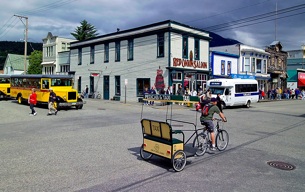 Alaska, Skagway. Visitors use a mulitude of methods to explore streets filled with colorful and historic store fronts in the goldrush town.