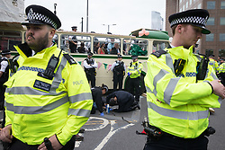 London, UK. 31st August, 2021. Police officers work to remove an Extinction Rebellion activist glued to the road alongside a vintage bus used to block a road junction to the south of London Bridge on the ninth day of their Impossible Rebellion protests. Extinction Rebellion are calling on the UK government to cease all new fossil fuel investment with immediate effect.