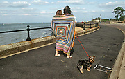 Yokshire Terrier pet dog looks backwards as its young owners walk away both covered in square-pattened beach blanket.