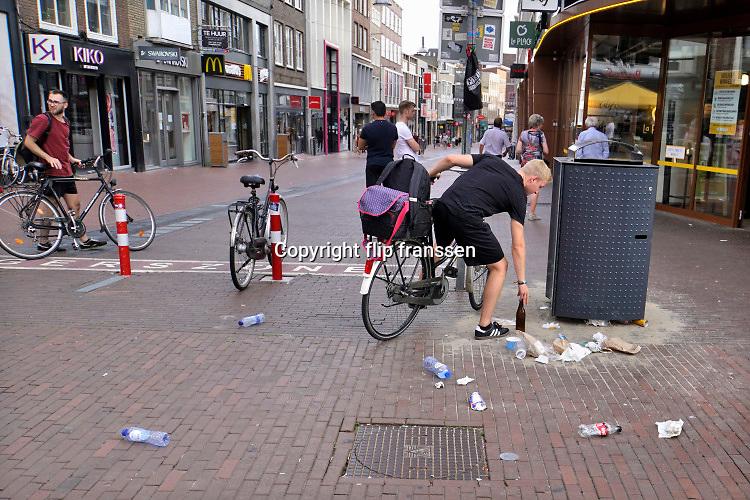 Nederland, Nijmegen, 18-7-2020 Een jonge man op de fiets zet een leeg bierflesje bij een afvalbak van de gemeente in de binnenstad . De bak is vol, propvol, en veel vuil ligt er al naast . Foto: ANP/ Hollandse Hoogte/ Flip Franssen