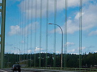 a single car in view while looking up at a Tacoma Narrows bridge tower and cables across the Tacoma Narrows of southern Puget Sound in western Washington state, USA