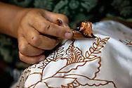 Making batik - detail shot of a woman applying wax using a wax pen called canting. Plentong, Yogyakarta, Central Java, Indonesia.