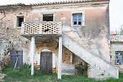 Derelict house with outside staircase in village of Peroulades in Northern Corfu, , Greece