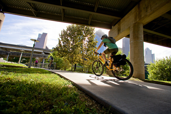 Three bicyclists riding on the pathway under an overpass in Buffalo Bayou park in Houston, Texas