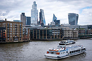Two boats pass by each other on the River Thames with the city of London skyline in the background on the 25th of May 2021 in London, United Kingdom.