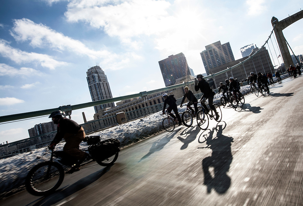 Racers make their way across the Hennepin Avenue bridge to Nicollet Island for the start of Stupor Bowl 17 in Minneapolis February 1, 2014. (Courtney Perry for MPR)