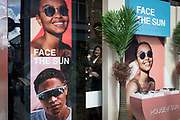 A shopper tries on sunglasses through the window of the window of the Sunglass Hut retailer in Covent Garden whose current slogan is 'Face the Sun', on 15th June 2019, in London, England.