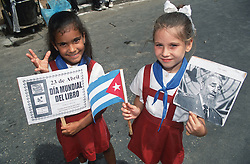 Two young girls wearing school uniform holding Cuban flag; portrait of Fidel Castro; and poster advertising World Book Day,