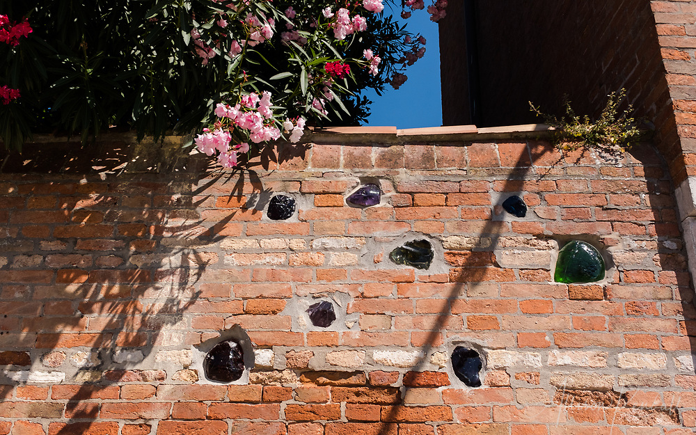 Chunks of glass embedded in a brick wall in Venice, Italy