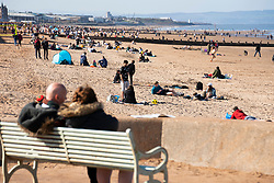 Portobello, Scotland, UK. 3 April 2021. Easter weekend crowds descend on Portobello beach and promenade to make the most of newly relaxed  Covid-19 lockdown travel restrictions and warm sunshine with uninterrupted blue skies. Pic; Beach is busy with small groups of people.  Iain Masterton/Alamy Live News