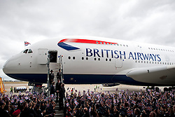 © London News Pictures.  04/07/2013 . London, UK.  British Airways staff wave union flags as the new British Airways AIRBUS A380 superjumbo arrives at Heathrow Airport. It was the first time British Airlines have taken delivery of the new plane, making British Airways the first European airline to operate both the 787 and A380. Photo credit : Ben Cawthra/LNP