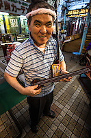 Sanshin three strings is a musical instrument from Okinawa.   The samsen is the precursor of the  shamisen in Jpan, sharing many characteristics. . The shamisen is sometimes called a Japanese banjo.  The Okinawa version is made of snakeskin, where the Japanese one uses cat skins for the body.
