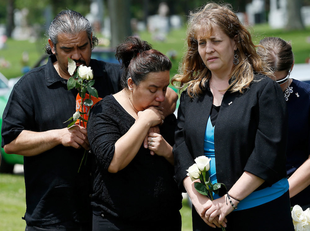 """""""Rest in His Arms"""" founder Susan Walker (R) and the grandparents of an abandoned newborn boy attend a burial service at All Saints Cemetery in Des Plaines, Illinois, United States, June 19, 2015. More than a year after he was found dead in a plastic shopping bag on a Chicago sidewalk, the baby boy was buried by a non-profit group """"Rest in His Arms"""" after abandoned by his teenage mother, who is charged with murder. REUTERS/Jim Young"""