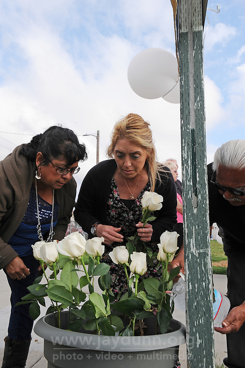"""Mary Lou Alejo, left, and Rita Castro tend flowers during Sunday's """"100 Mothers Vigil"""" for Azahel Cruz in Salinas. The 6-year-old was struck in the head and killed by a stray bullet during a nearby gang shootout on March 23rd, 2010."""