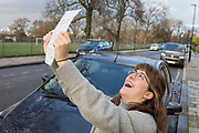 A young 23 year-old woman celebrates the passing of her driving test by holding up her test certificate in front of the family car in south London, on 7th December 2018, in London England.