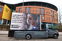 "© Licensed to London News Pictures. 05/03/2021. Salford, UK. A digital billboard showing a photograph of a nurse wearing PPE and the words "" Look them in the eyes and tell them they're only worth an extra £3.50 a week "" is seen outside Salford Royal Hospital . The British Government has proposed a one percent pay increase to nurses' salaries . Photo credit: Joel Goodman/LNP"