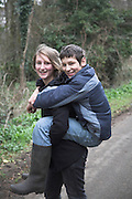 Model released girl and boy twins with sister giving her brother a piggy-back ride, UK
