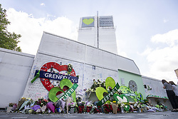 June 14, 2018 - London, UK - Members of the public pay their respects at a memorial at the foot of Grenfell Tower on the first anniversary of the Grenfell Tower Fire in which 72 people were killed. Grenfell Tower caught fire on the night of June 14, 2017 after a small blaze started in one of the flats which spread rapidly up the outside of the 24-floor tower block. A public inquiry is currently underway. (Credit Image: © Rob Pinney/London News Pictures via ZUMA Wire)