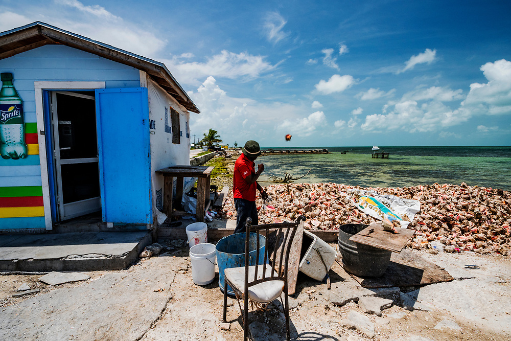 A former fisherman who now specializes in removing the conch from its shell throws another one on the pile in West End, Grand Bahama.