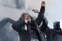 """London, April 16th 2016. A young woman celebrating her birthday and surrounded by black-clad protesters clutches a bottle of Cava as anarchists let off a smoke bomb on the plinth of Nelson's column in Trafalgar Square after thousands of people supported by trade unions and other rights organisations demonstrated against the policies of the Tory government, including austerity and perceived favouring of """"the rich"""" over """"the poor""""."""