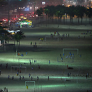 Locals play football at night under floodlight on Copacabana Beach, Rio de Janeiro, Brazil. 21st July 2010. Photo Tim Clayton.