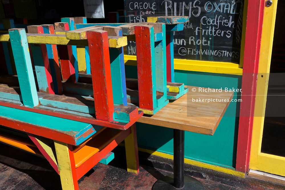 As the UK government considers further restrictions of movement in public places and the continued forced closure of restarants, cafes, gyms and cinemas etc. during the Coronavirus pandemic, empty seating is stacked outside a food business in Brixton Market, on 23rd March 2020, in London, England.