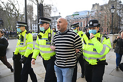 © Licensed to London News Pictures. 19/12/2020. London, UK. A protester is arrested by police officers for taking part in an Anti Covid-19 lockdown demonstration in Central London. The group against the current tier regulations and vaccination for the Covid-19 disease. Photo credit: Ray Tang/LNP