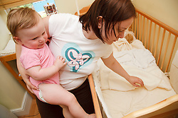 Mother putting baby into cot