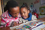 Two African children read a story book together as part of the 'book buddy' scheme in Zenzeleni School in Khayelitsha township, Cape Town, South Africa.  The book buddy scheme is supported by the Shine Centre which is a charity that aims to address the high illiteracy rate in South Africa by improving literacy levels among children in schools and disadvantaged communities. Children of similar reading ability are paired together to read to each other.