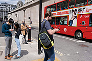 Pedestrians check their phones as a London bus drives past the high walls of the Bank of England in the City of London, the capitals financial district, on 27th May 2021, in London, England.