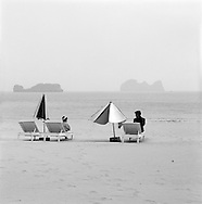 Vietnamese family sits on beach chairs along the shore of Cat Ba Island, Vietnam, Southeast Asia. December 2004.